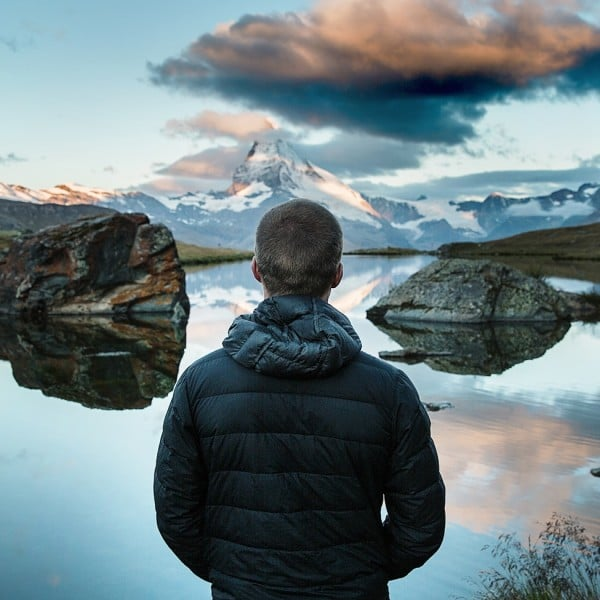 man in front of mountain lake